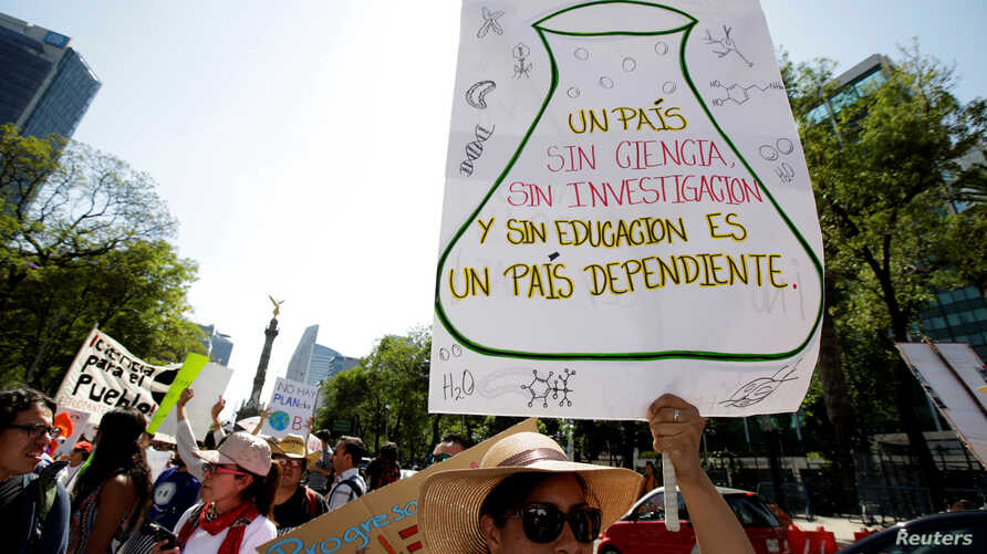 """FILE - A demonstrator holds a placard as she participates in the March for Science rally on Earth Day in Mexico City, Mexico April 22, 2017. The placard reads: """"A country without science, research and education is a country dependent."""" Earth Day 2018"""