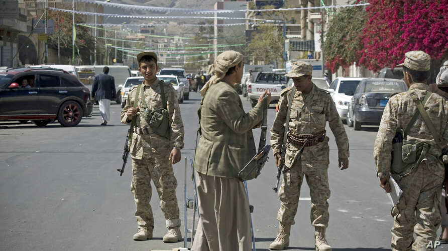 Shi'ite Yemeni Houthi, wearing army uniforms stand guard on a street leading to the presidential palace in Sana'a,  Jan. 21, 2015.