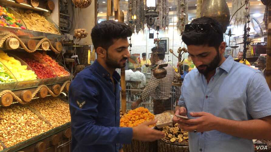 Saman Sadq, left, in his family's sweets and nuts shop, says that for him, Kurdish independence is a natural right, in Erbil, Kurdish Iraq, Sept. 5, 2017.