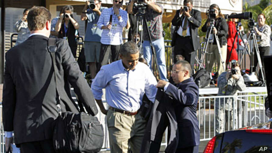 U.S. President Barack Obama dons his jacket before boarding Air Force One at Hickam Air Force Base in Honolulu November 15, 2011