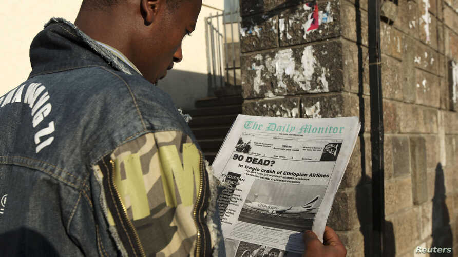 FILE - A man reads a newspaper as he walks along a street in Addis Ababa.