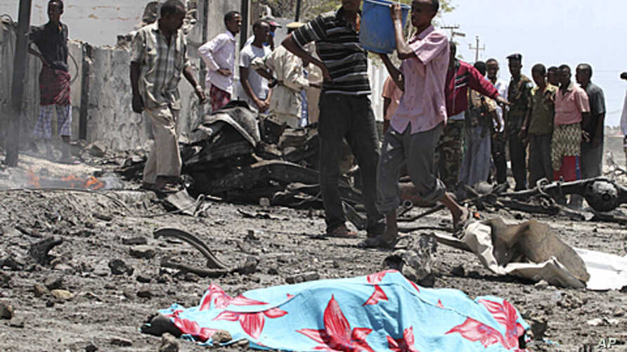 Residents gather near the covered remains of a suicide bomber at the scene of an attack along a street in Somalia's capital Mogadishu. A truck bomb killed at least 65 people at government buildings in the heart of Somalia's capital on Tuesday, an amb