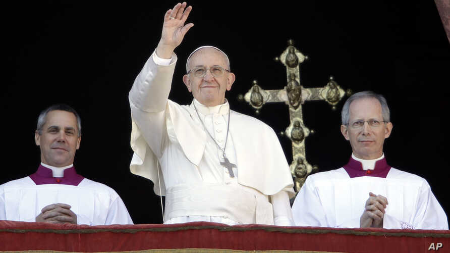 Pope Francis, flanked by Master of Ceremonies Bishop Guido Marini, waves to faithful during the Urbi et Orbi Christmas' day blessing from the main balcony of St. Peter's Basilica at the Vatican, Dec. 25, 2017.