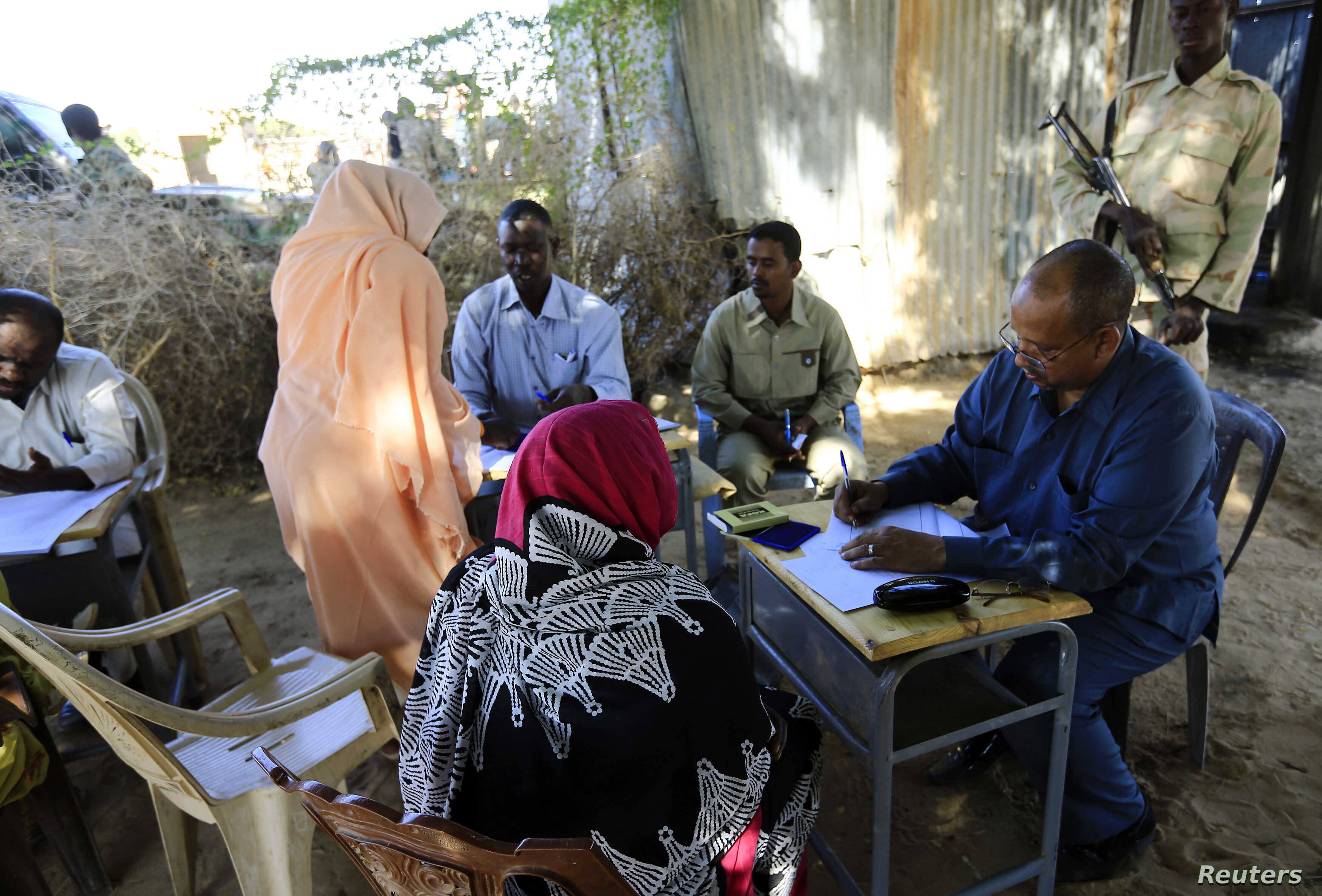 FILE - Yasir Ahmed Mohamed, seated at right, special prosecutor for crimes in Darfur, and his team talk to women during an investigation into allegations of mass rape in Thabit, North Darfur, Nov. 20, 2014.