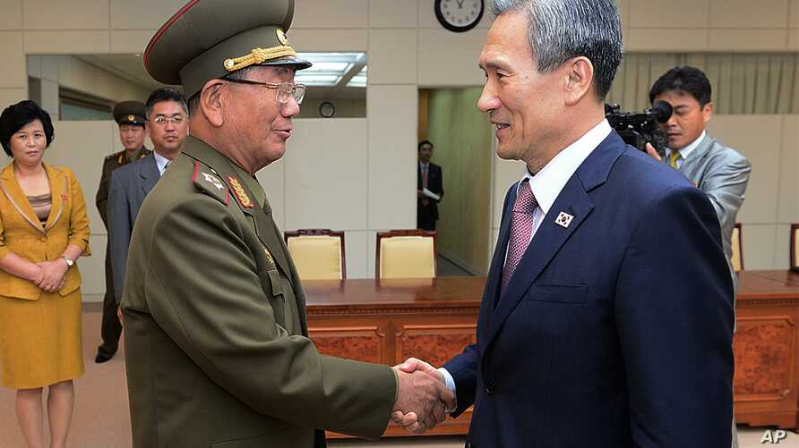 South Korean presidential security adviser Kim Kwan-jin, right, shakes hands with Hwang Pyong So, North Korea's top political officer for the Korean People's Army, after meeting at the border village of Panmunjom in Paju, South Korea, Aug. 25, 2015.