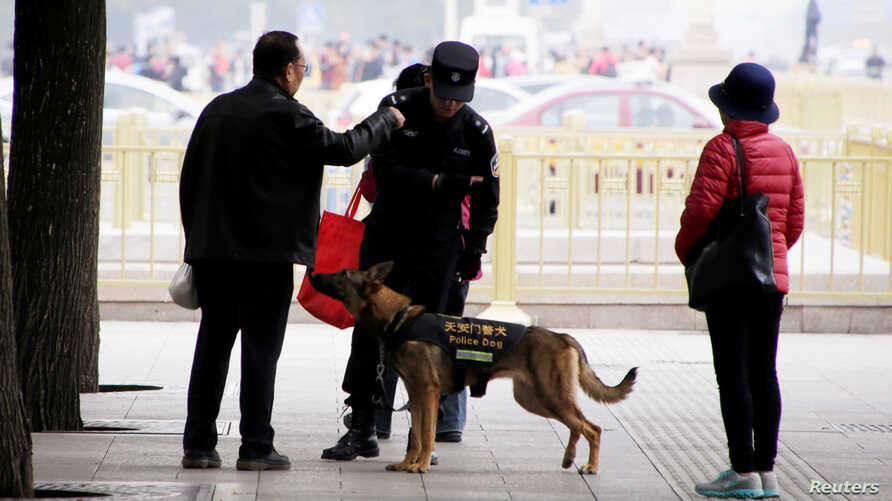A police dog patrols next to Tiananmen Square on the first day of a plenary session of the 18th Central Committee of the Communist Party of China, in Beijing, China, Oct. 24, 2016.