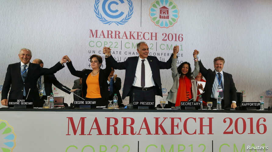 U.N. climate chief Patricia Espinosa, second left, Morocco's Foreign Minister Salaheddine Mezouar, center, and Council of Europe Goodwill Ambassador Bianca Jagger, second right, celebrate after the proclamation of Marrakech, at the U.N. World Climate