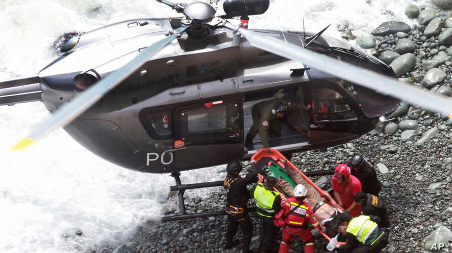 In this photo provided by the government news agency Andina, rescue workers surround an injured man on a stretcher who was lifted up from the site of a bus crash at the bottom of a cliff, after the bus was hit by a tractor-trailer rig in Pasamayo, Pe