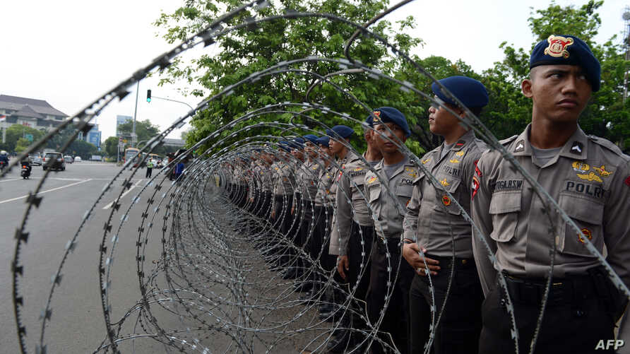 Indonesian police stand behind barb wire outside the presidential palace as demonstrators from an Indonesian university held a protest against the oil price increase across the street in Jakarta, Nov. 19, 2014.