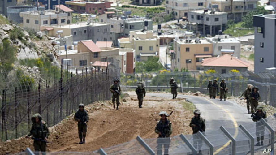 With the Druze village of Majdal Shams in the background, Israeli troops patrol along the border between Israel and Syria the Golan Heights, May 20, 2011
