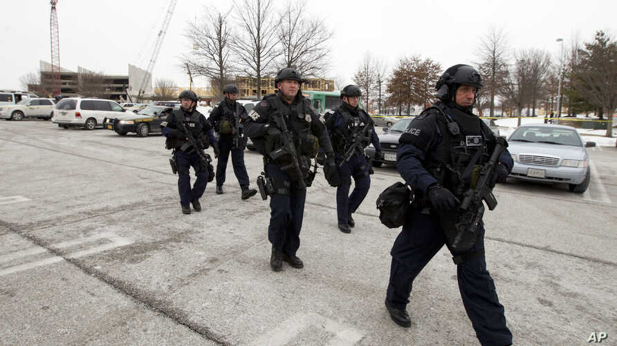 Police move in from a parking lot to the Mall in Columbia after reports of a multiple shooting, Saturday Jan. 25, 2014 Howard County, Md.