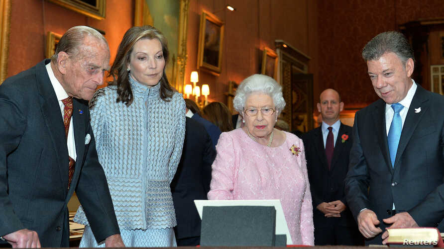 From left, Britain's Queen Elizabeth, Prince Philip, Colombia's President Juan Manuel Santos and his wife, Maria Clemencia Rodriguez de Santos look at Colombian items from the Royal collection in the picture Gallery of Buckingham Palace, November 1,