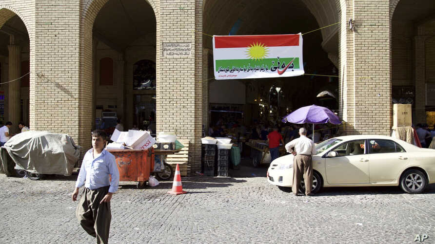 "FILE - A man walks past a campaign slogan printed on a Kurdish flag urging people to vote ""yes"" in the upcoming poll on independence from Iraq, in Irbil, Iraq, Aug. 24, 2017."
