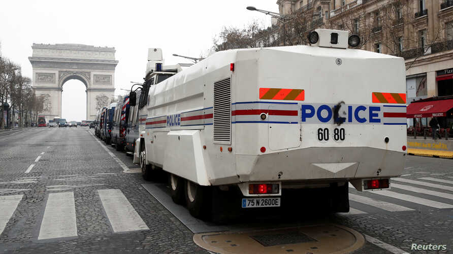 """A French police water canon vehicle is in place on the Champs-Elysees avenue during the the 19th consecutive national protest Saturday of the """"yellow vests"""" movement in Paris, March 23, 2019."""