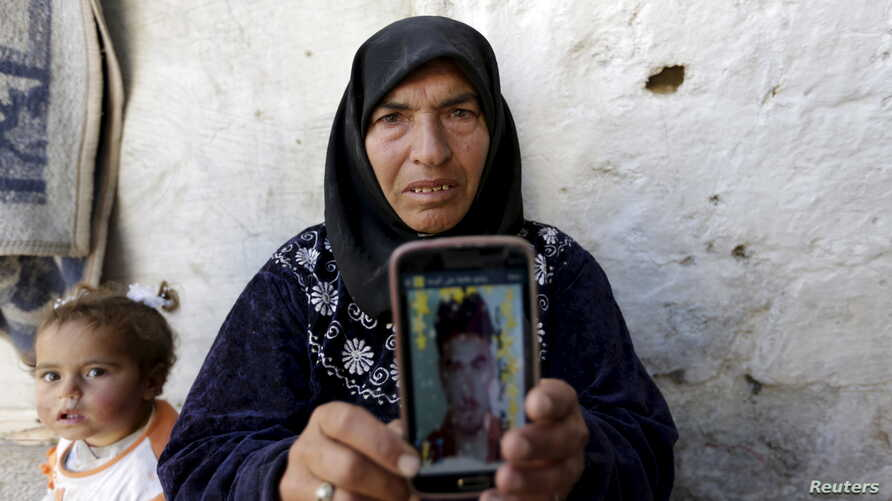 Amal Ibrahim, 57, shows a picture of one of her sons, Mohammad, in rebel-held Kafrouma village near Idlib, Syria, March 20, 2016. Authorities detained her two sons, and she said she was told that one of them, Abdullah, had died from torture. She said