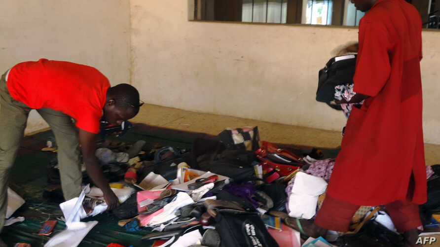 A student aided by a porter rummages through personal effects abandoned by students at the Federal College of Education in the northern Nigerian city of Kano, Nigeria, Sept. 17, 2014, following an attack by gunmen who stormed the lecture hall opening