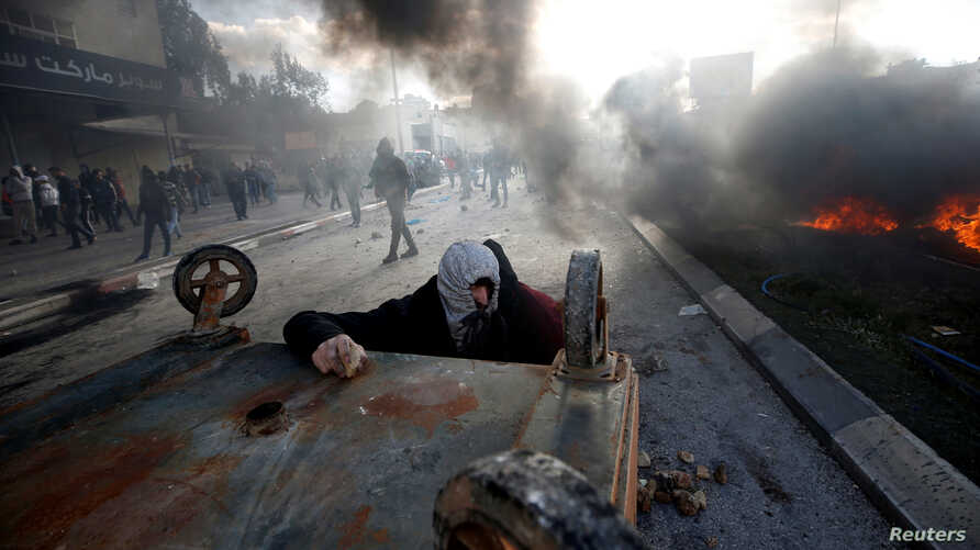 A Palestinian protester takes cover during clashes with Israeli troops at a protest against U.S. President Donald Trump's decision to recognize Jerusalem as the capital of Israel, near the Jewish settlement of Beit El, near the West Bank city of Rama