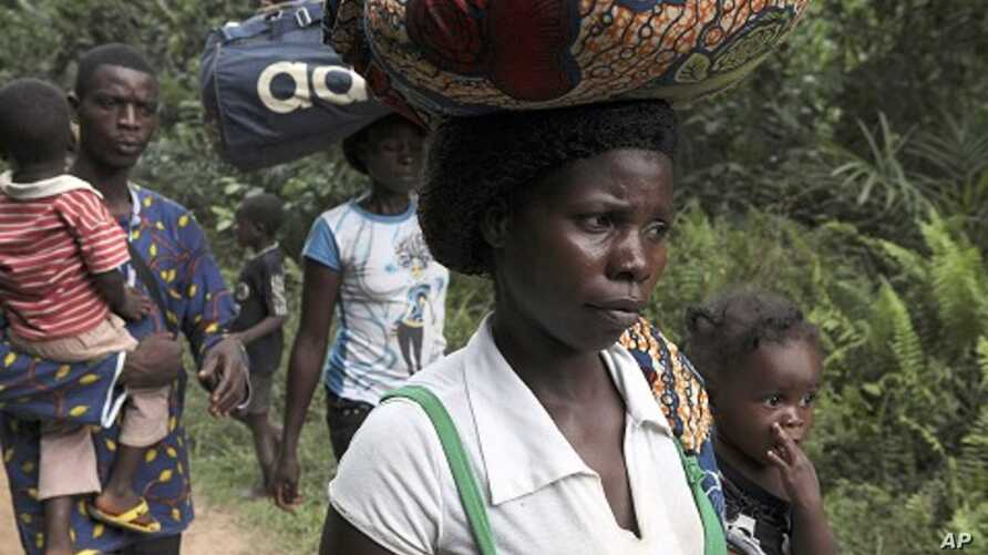 Refugees from Ivory Coast walk with their their belongings through Grand Gedeh county in eastern Liberia March 23, 2011.