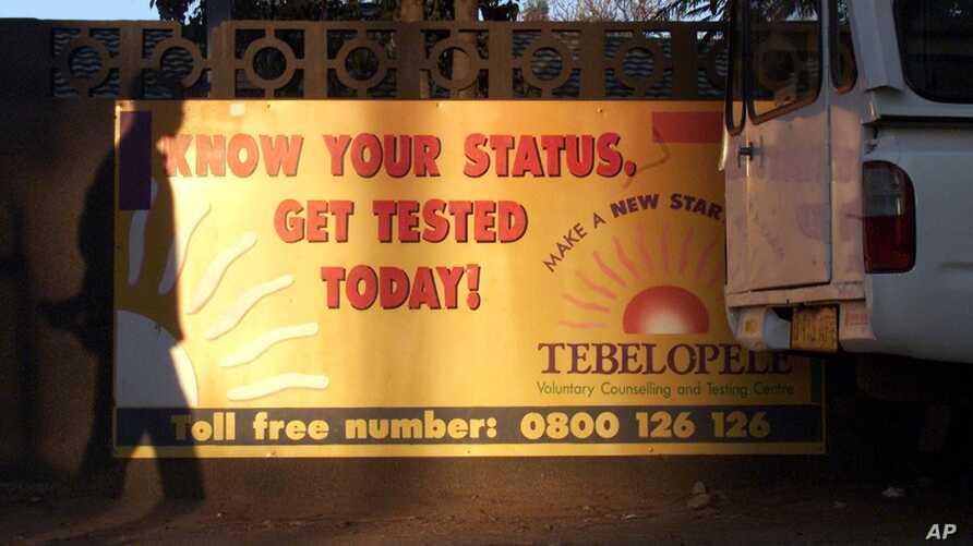 FILE - The shadow of a pedestrian is cast over a banner for a HIV testing center in Gaborone, Botswana.