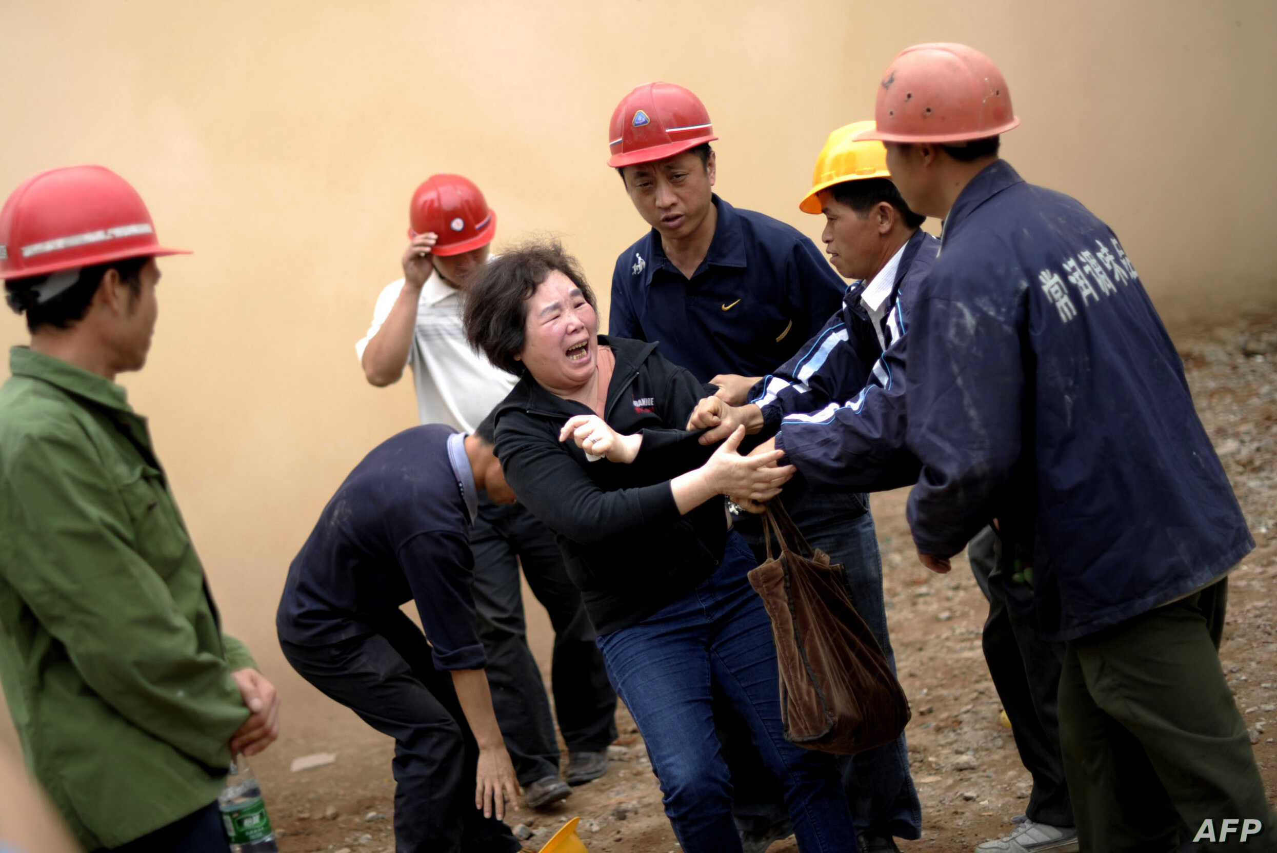 Huang Sufang (C) attempts to protect her home as workers move in for demolition orders in Yangji village, Guangzhou, south China's Guangdong province on March 21, 2012.