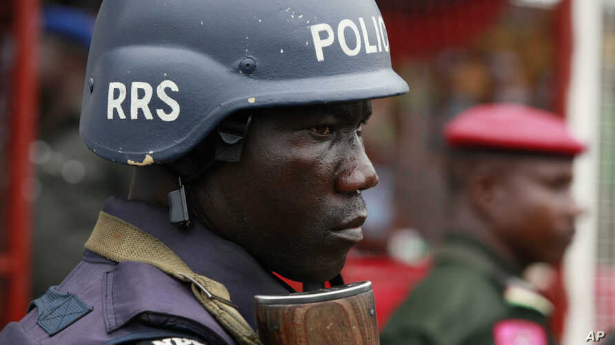 FILE - A police officer stand guards during a demonstration in Lagos, Nigeria, May. 1, 2014. An elite Nigerian police squad set up to combat violent crime is torturing detainees to extract lucrative bribes and confessions, an new Amnesty Internationa