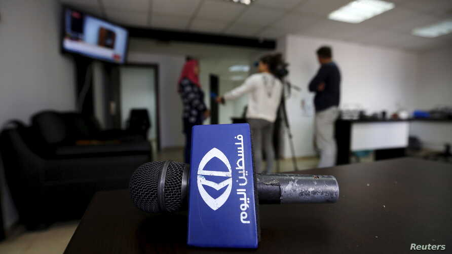 Journalists interview an employee as the logo of the Palestine Today TV station is seen following a raid by Israeli forces in the West Bank city of Ramallah, March 11, 2016.