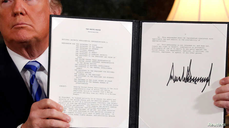 U.S. President Donald Trump holds up a proclamation declaring his intention to withdraw from the JCPOA Iran nuclear agreement after signing it in the Diplomatic Room at the White House in Washington,  May 8, 2018.