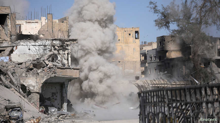 Smoke rises after a landmine is exploded as fighters of Syrian Democratic Forces clear roads after the liberation of Raqqa, Syria Oct. 18, 2017.