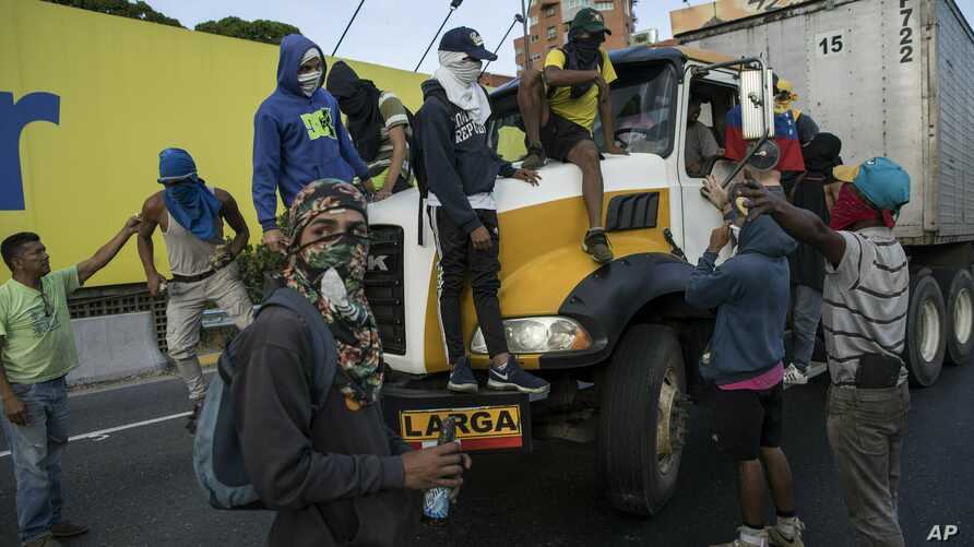 Anti-government protesters stop a truck while blocking a highway with a small group of demonstrators who were returning from a peaceful demonstration called by self-declared interim president Juan Guaido to demand the resignation of President Nicolas