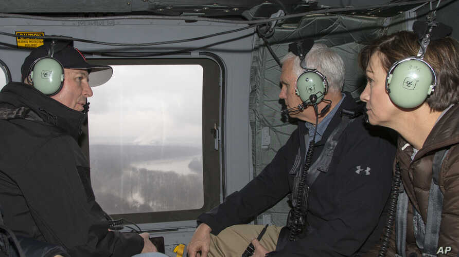 Vice President Mike Pence, center, tours in a helicopter over areas flooded by the Missouri and Elkhorn rivers, with Iowa Gov. Kim Reynolds, right, and Neb. Gov. Pete Ricketts, left, March 19, 2019.