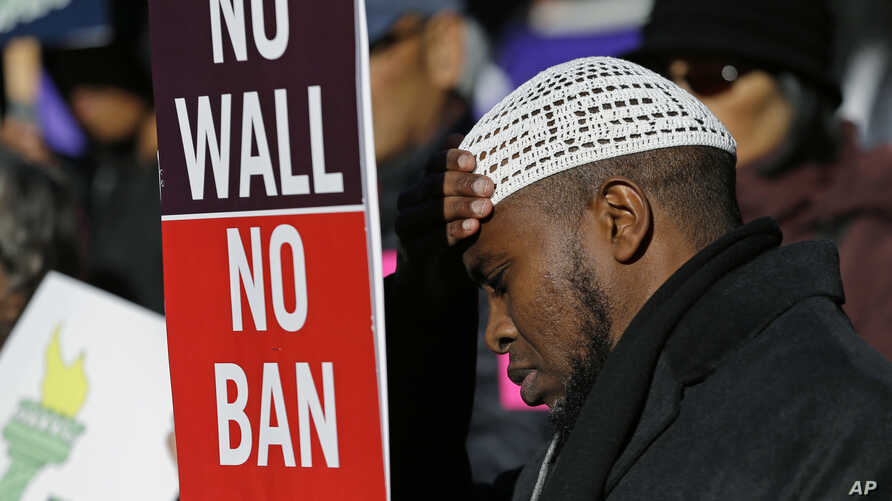 "FILE - Abdirahman ""OJ"" Mohamed, of Seattle, holds a sign that reads ""No Wall No Ban,"" during a protest against federal efforts to restrict immigration, Dec. 6, 2017, outside a federal courthouse in Seattle."