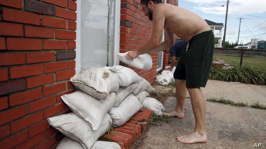 Adam Bazemore places sandbags in the doorways, Sept. 11, 2018, in the Willoughby Spit area of Norfolk, Va., as he makes preparations for Hurricane Florence.