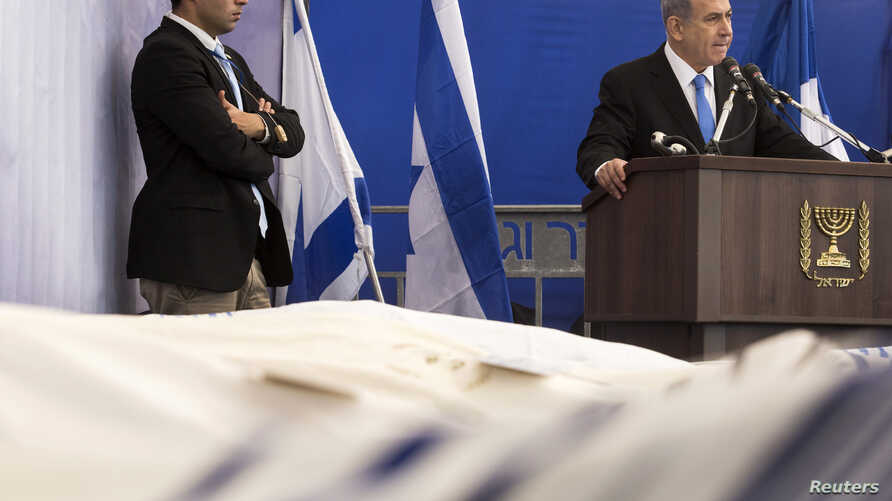 Israel's PM Benjamin Netanyahu (R) delivers a speech near the covered bodies of Yohan Cohen, Yoav Hattab, Philippe Braham and Francois-Michel Saada, victims of Friday's attack on a Paris grocery, during their joint funeral in Jerusalem, Jan. 13, 2015