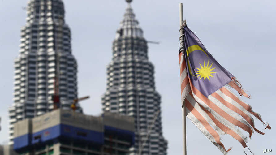 FILE - A battered Malaysian national flag flies in front of the Petronas Towers in Kuala Lumpur, Malaysia, April 10, 2018. Malaysia's government says it will abolish the death penalty and halt all executions.