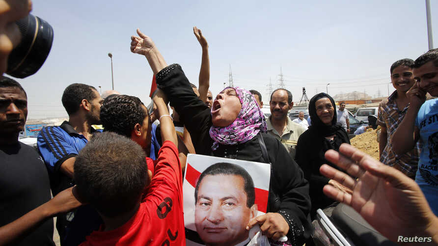A supporter of former president Hosni Mubarak holds his poster to celebrate as she waits for his release in front of the main gate of Tora prison, Cairo, August 22, 2013.