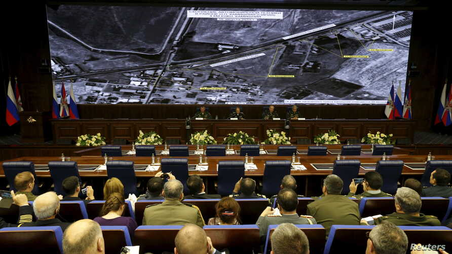 Defence ministry officials sit under screens with satellite images on display during a briefing in Moscow, Russia, Dec. 2, 2015. Russia's defence ministry said on Wednesday it had proof that Turkish President Tayyip Erdogan and his family were benefi