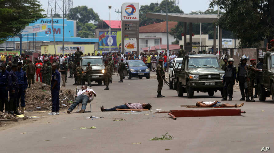 The bodies of people killed during election protests lie in the street, as Congolese troops stand near by in Kinshasa, Democratic Republic of Congo, Sept. 19, 2016.