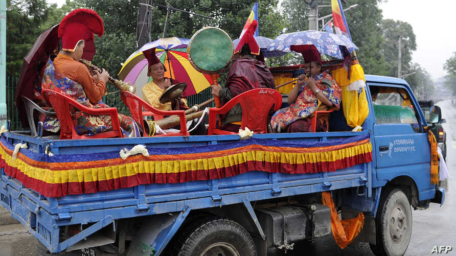Nepalese monks playing instruments on a truck take part in a procession to mark the 9th International Everest Day in Kathmandu, May 29, 2016.