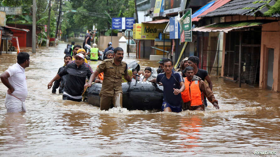 FILE - Rescuers evacuate people from a flooded area to a safer place in Aluva in the southern state of Kerala, India, Aug. 18, 2018.