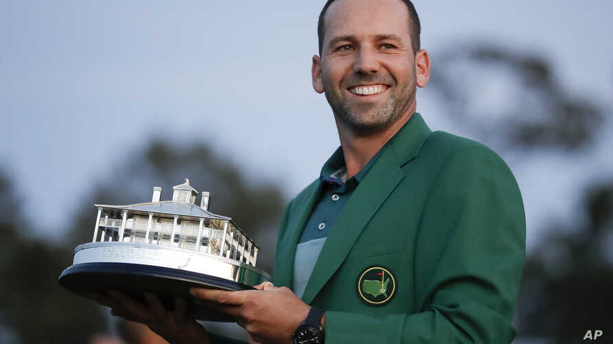 Spain's Sergio Garcia holds the first-place trophy while wearing the winner's green jacket after taking after Masters' title in a playoff, April 9, 2017, in Augusta, Georgia.