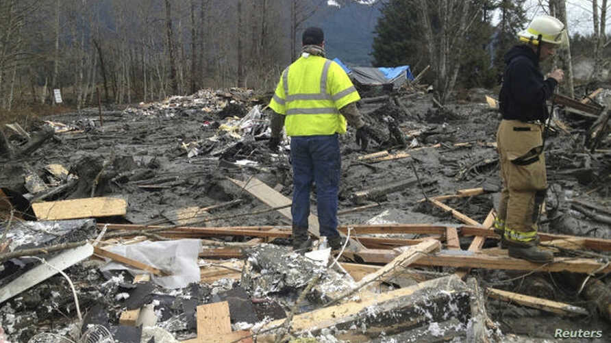 Officials survey a large mudslide in this handout photo provided by the Washington State Police near Oso, Washington March 22, 2014. The mudslide pushed debris and at least one house onto Highway 530 near Oso Saturday morning according to local news ...