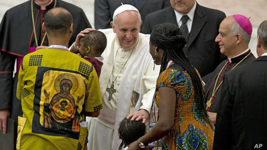 """Pope Francis greets a family in the Paul VI hall at the Vatican at the end a meeting with participants in the """"Evangelii Gaudium"""" conference organized by the Pontifical council for the new evangelization, Sept. 19, 2014."""