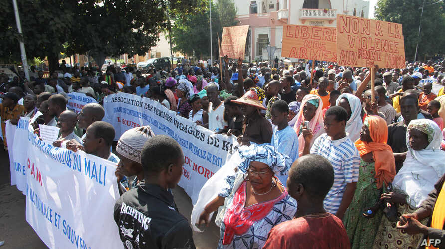 People holding banners take part in a protest called by the Coordination of Patriotic Organizations in Mali (COPAM) against a foreign military intervention in Mali to reclaim the Islamist-controlled north, September 28, 2012.