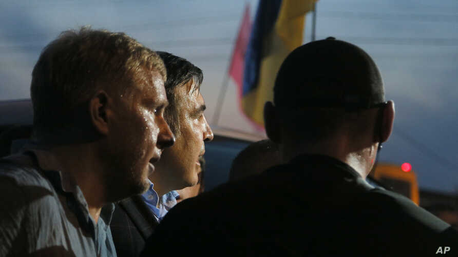 Former Georgian president and ex-governor of Ukraine's Odessa region  Mikheil Saakashvili, center, is surrounded by supporters at Shehini checkpoint on Ukraine's border with Poland, in Shehini Ukraine, Sept. 10, 2017.