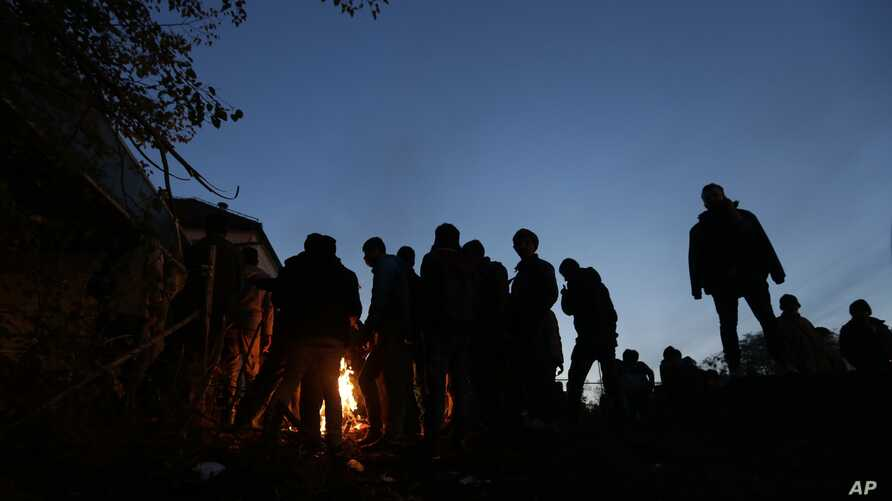 Migrants warm up by fire while waiting to enter a camp in Spielfeld, Austria, Sunday, Oct. 25, 2015.