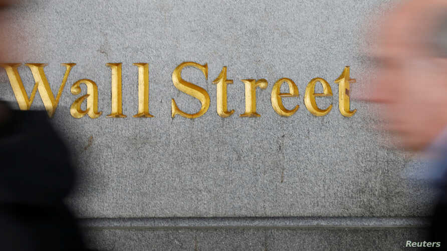 FILE - People walk by a Wall Street sign close to the New York Stock Exchange in New York.