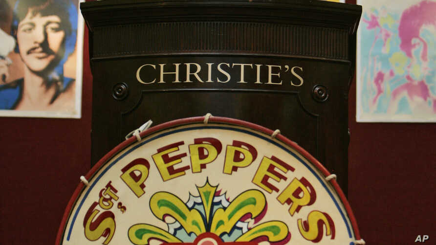 An auction worker gestures before the sell of a drum featured on the cover of the famous Beatles' Sgt. Peppers Lonely Hearts Club Band album, at Christie's in London, July 10, 2008. The drum sold for $890,000.