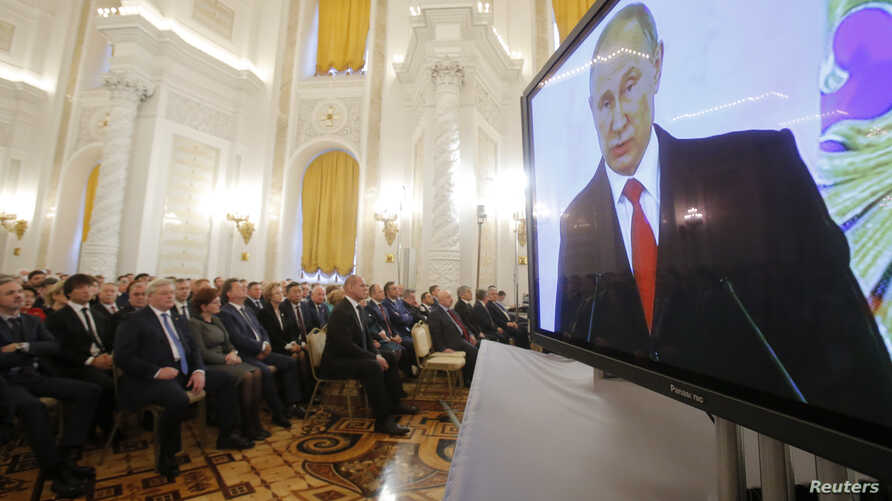 Russian President Vladimir Putin is seen on a screen during his annual state of the nation address at the Kremlin in Moscow, Russia, December 1, 2016.