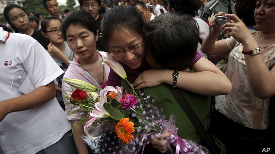 "A Chinese student is greeted by a relative after taking the annual college entrance examinations in Beijing, June 8, 2010. Each year, about over 10 million high school seniors across China take the ""gaokao."""