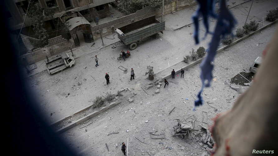 People inspect the damage at a site hit with airstrikes by pro-Syrian government forces in the rebel held Douma neighborhood of Damascus, Syria, Feb. 14, 2016.